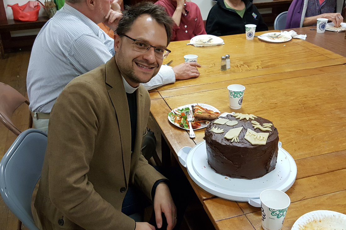 Photograph of the Rev. Reed Carlson, Saint Peter's Christian Formation Associate, enjoying a cake at a Wednesday Adult Forum