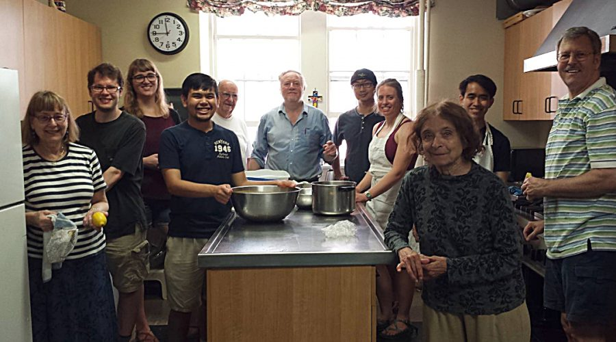 Photograph of a CommonCare crew gathering in the kitchen before meal preparation begins