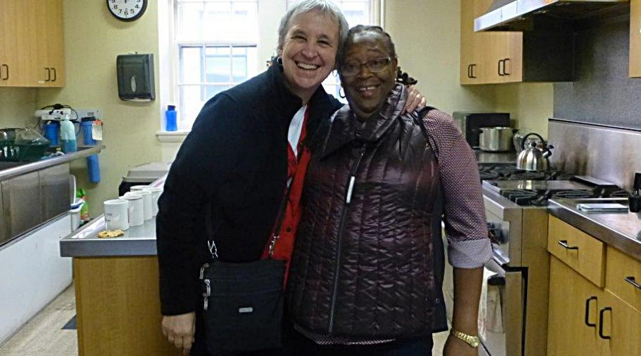 Photo of two good friends embracing in the kitchen at Saint Peter's Episcopal Church
