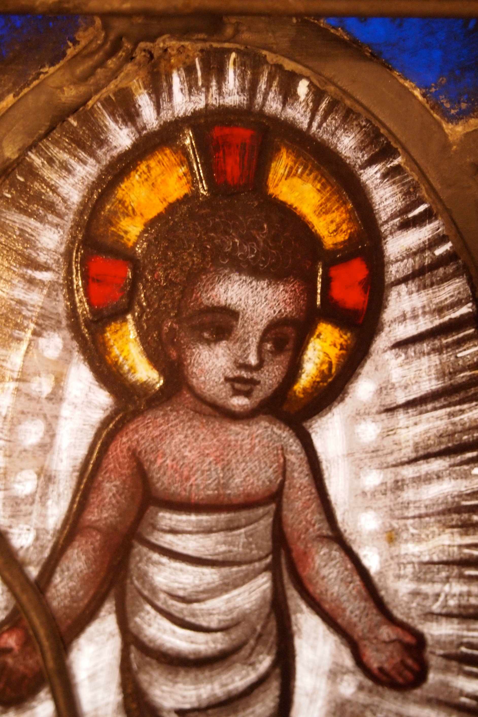 Detail of Saint Peter's stained glass nativity window showing Christ as an infant