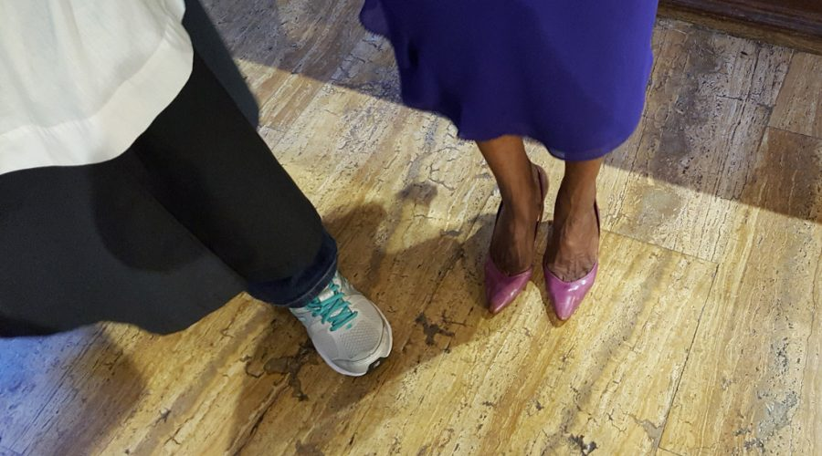 Photograph of the feet of two parishioners, one wearing tennis shoes under a choir robe and the other wearing heels